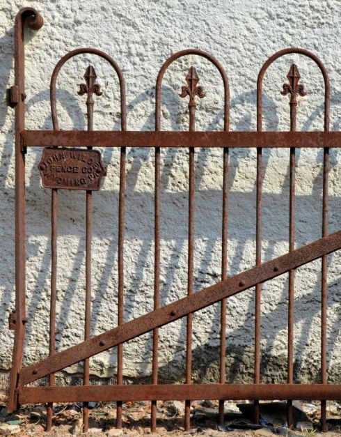 "This gorgeous wrought iron fence contains a ""makers mark"" which tells us that this piece was fashioned by a fence company in Pennsylvania."