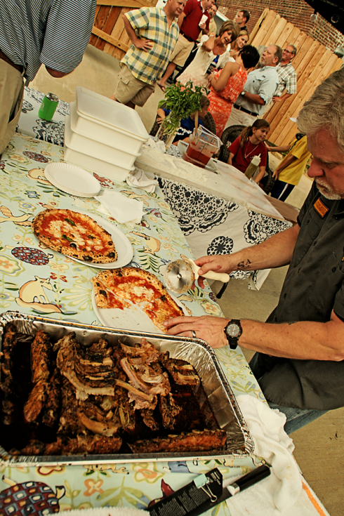 Clifton Holt of Little Savannah Restaurant serves up pizza and ribs.
