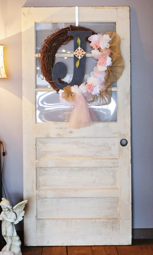 Two salvaged white doors were used at the entrance of the venue to display hand crafted wedding wreaths.
