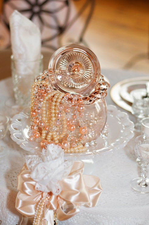 Antique and vintage glass pieces in a combination of clear, white, and pink glass were used on every table to add a touch of elegance to the vintage themed wedding.