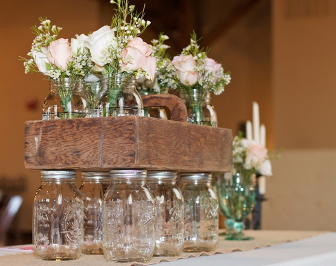 Mason jars were displayed in an old wood box and used to hold the bridesmaids bouquets both before and after the ceremony.