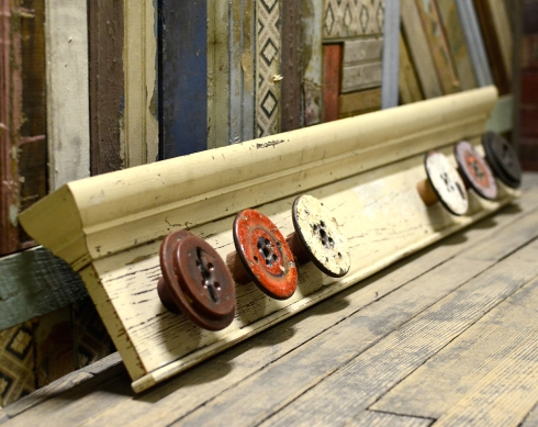 Cornice board built from salvaged trim and industrial wood thread spools.