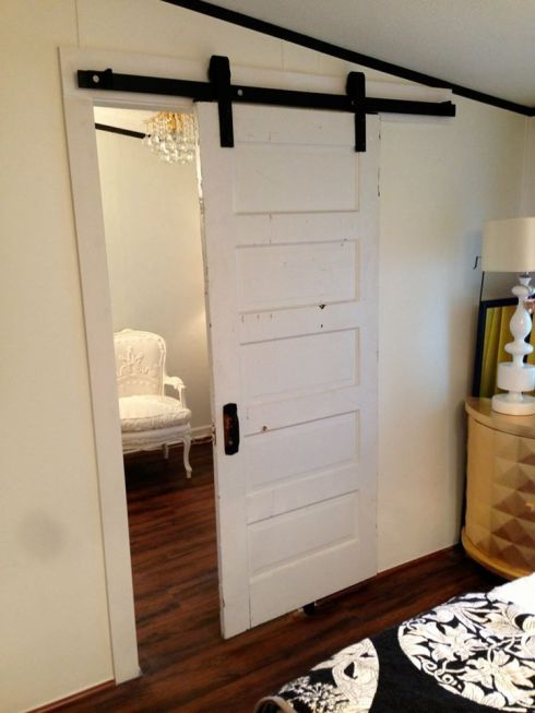 Salvaged door from Southern Accents installed in a bedroom as a sliding door.